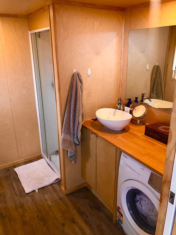 ply bathroom in a Tiny Home showing counter top sink and washing machine
